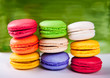 Colorful macaroons isolated against a green background