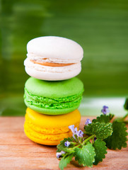 A stack of three colorful French macarons on a green background