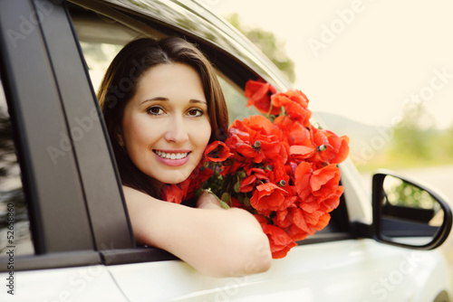 girl in car with flowers