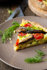 slice of quiche with vegetables and fish, sprats