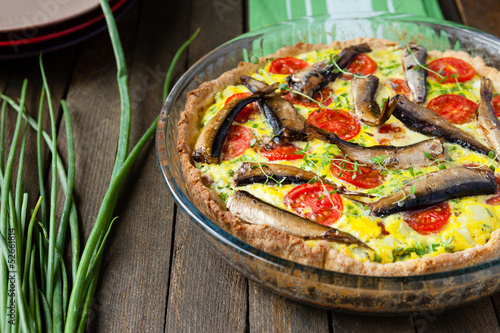 Homemade quiche with vegetables and fish, sprats