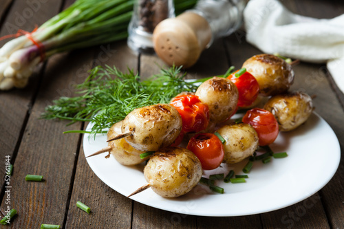 potatoes in their skins, and tomatoes on skewers