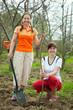 Happy women planting fruit tree