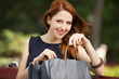 Style redhead women sitting on the bench with shopping bags