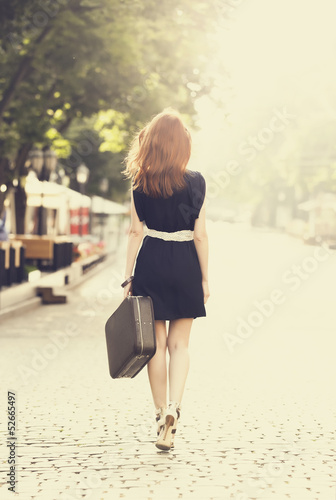 Young woman with suitcase walking on the city street