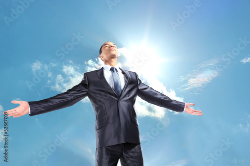 Happy businessman standing outside with arms outstretched