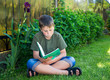 boy with a book on the grass