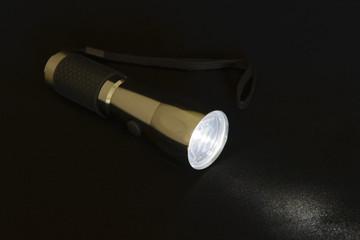 Включенный электрический фонарик изолированный на черном фоне