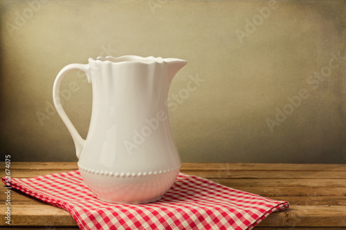 White jug on tablecloth on wooden table over grunge background