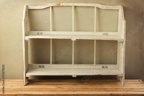 Vintage shelf on wooden table over grunge background