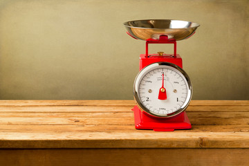 Retro style scales on wooden table over grunge background