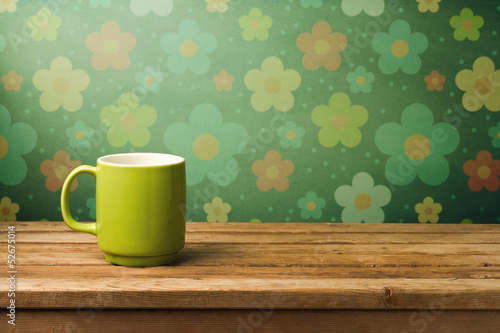 Green mug on wooden table over floral wallpaper - 52675014