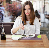 Young woman eating sushi in an Asian restaurant