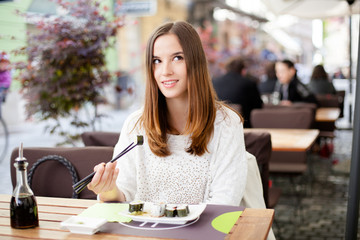 Young woman daydreaming while eating sushi