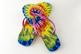 Colorful tie-dye patterned flip flops on a white background