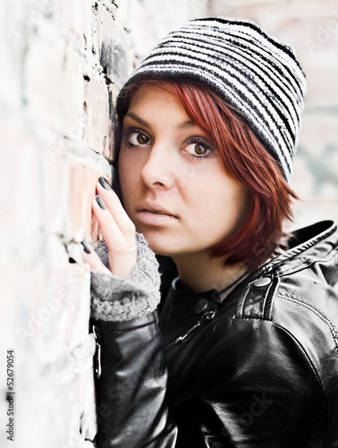 Portrait of young woman at a brick old wall
