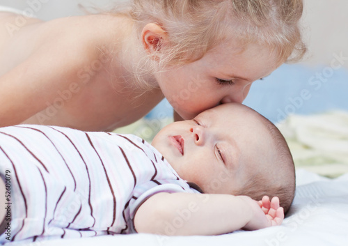 little sister kissing baby brother