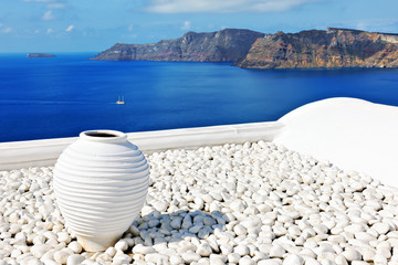 Clay jar on rooftop with Aegean Sea in background, Oia