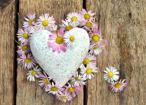 Herz aus Gänseblümchen auf Holzbrett mit Marmorzerz