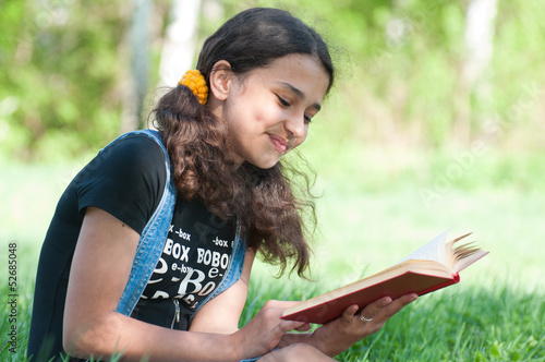 Teen girl reading a book on nature