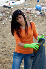 Young woman with bag full of dirt on destroyed dirty beach