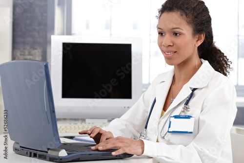 Young doctor working on laptop computer smiling