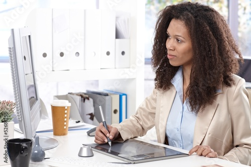 Young designer at desk with drawing pad