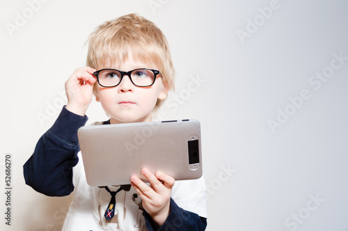 Little boy reading on tablet pc