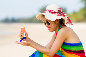 Sunscreen woman. Girl putting sun block on beach holding