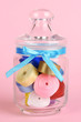 Glass jar containing various colored ribbons on pink background