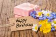 Geburtstagsgeschenk mit Blumen und Karte