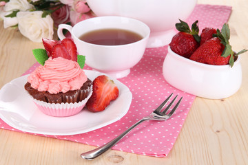 Beautiful strawberry cupcake and flavored tea