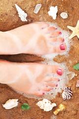 Смешно загорелые ноги на желтом песке пляжа