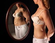 Schlanke Frau sieht sich dick im Spielgel
