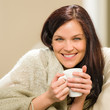 Portrait of joyful woman drinking hot beverage