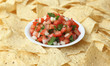 A bowl of pico de gallo surrounded by tortilla chips