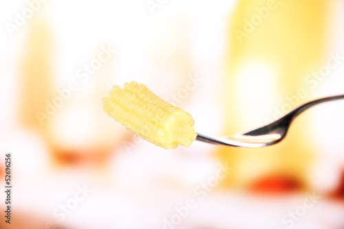 Baby corn sticking on fork, on bright background