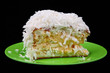coconut cake piece on green plate isolated on black