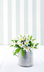 Flowers in a metal cup on vintage background