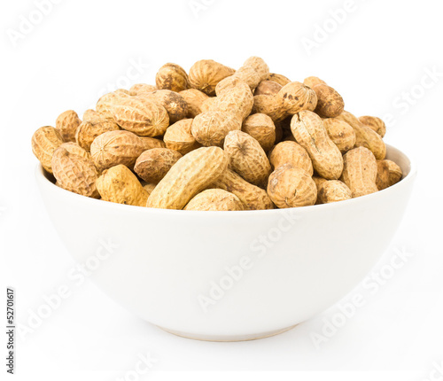 Raw shelled great peanuts in a bowl on white background, closeup