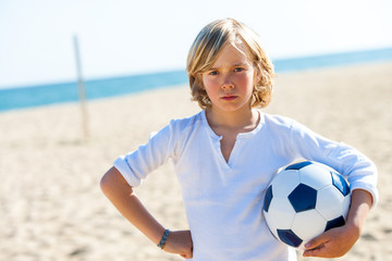 Upset boy holding soccer ball outdoors.