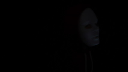 Horror masked man with torch in darkness
