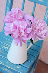 Bunch of peony on shabby blue chair