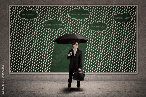 Businessman using umbrella to protect business loss