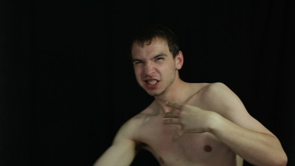 Aggressive shirtless man over dark background