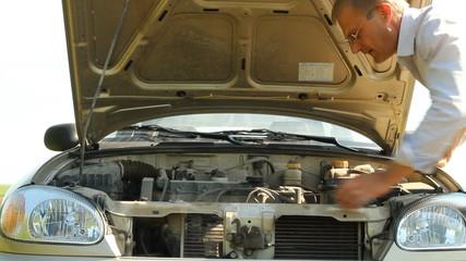 Man troubleshoot a broken car under the hood