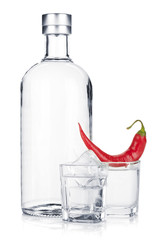Bottle of vodka and shot glass with ice and red chili pepper