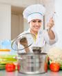beautiful cook  in toque prepares veggie lunch