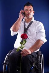 junger Mann im Rollstuhl telefoniert