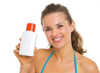 Portrait of woman in swimsuit holding bottle of sun block creme